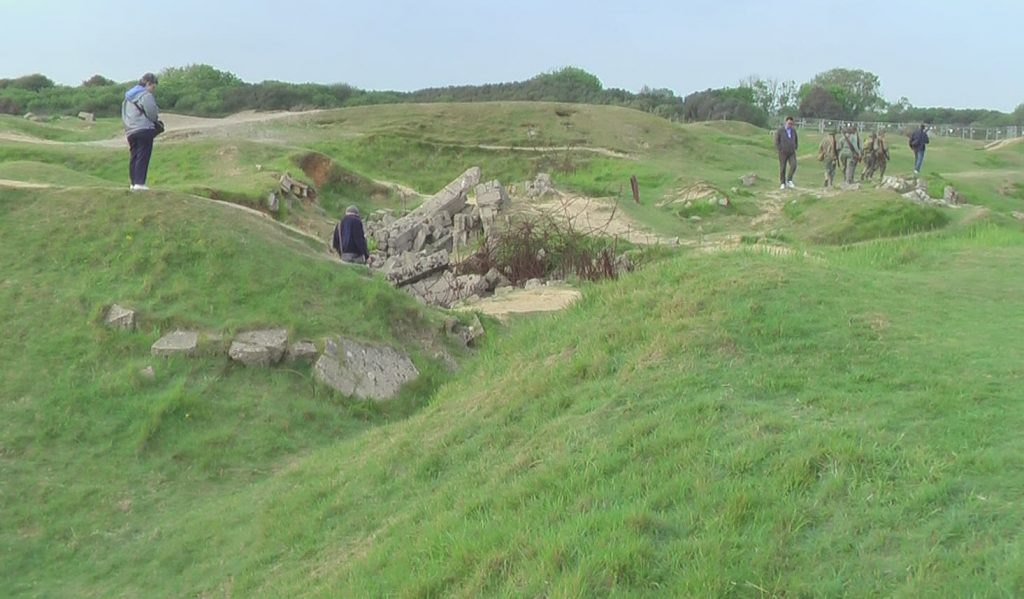 Pointe du Hoc; Shell holes and destroyed concrete bunker.